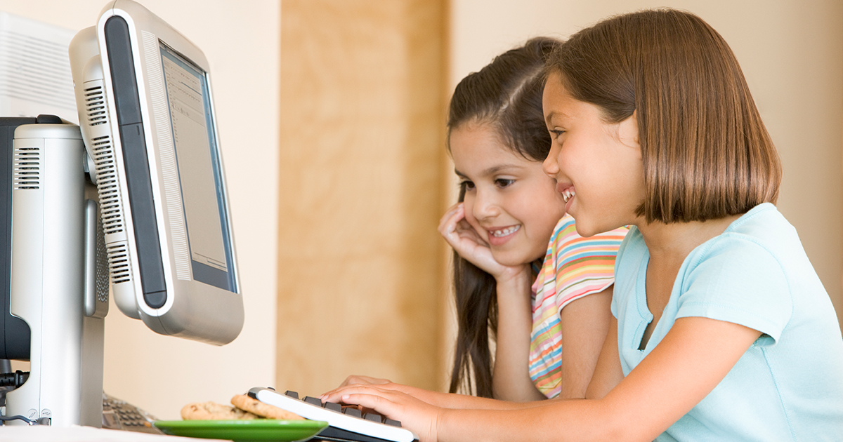 Two young girls using a home computer to complete school work